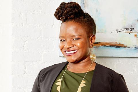 Chinyere Ezie. Smiling Black woman with locs in a high bun and shaved sides, wearing a green shirt, dark suit jacket and gold earrings and necklace.