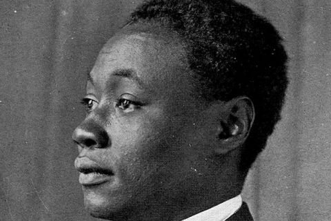 Claude McKay. Archival black and white photo of side profile of Black man wearing a white shirt and dark suit jacket.