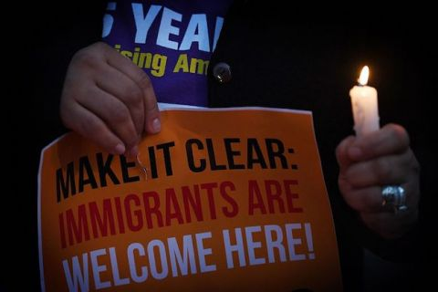 "close up of a person holding a lit candle next to a sign that reads, ""make it clear, immigrants are welcome here"""