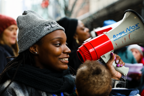 Dashara, a Black woman with a baby strapped to chest, holds a red megaphone at the Walmart protest.
