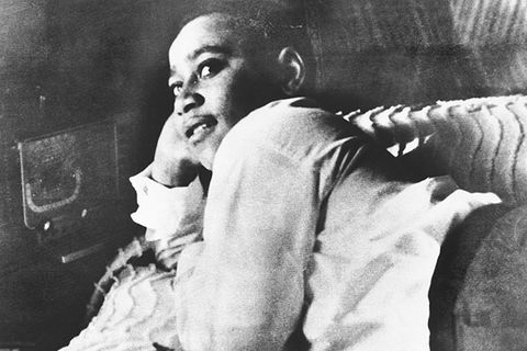 Emmett Till. Archival photo of young Black boy reclining on a bed with his head in right hand, wearing a white shirt and dark pants.