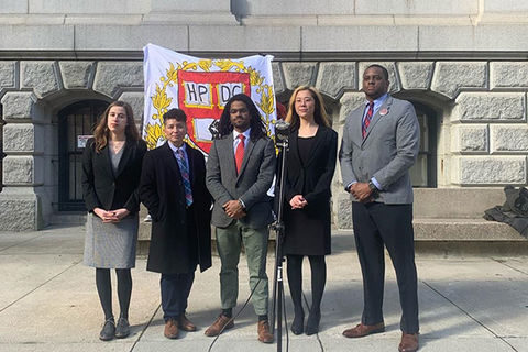 Harvard students. Five students stand side-by-side. Two Black men wearing gray suits, one White woman wearing black jacket and gray dress, Asian American woman wearing all black dress and black jacket, Latinx person wearing black coat, colorful tie, white shirt.