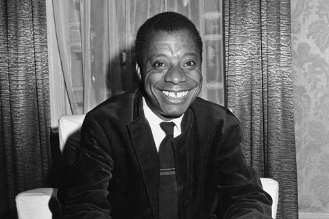 James Baldwin. Black man with short dark hair smiling broadly, wearing a white shirt and dark suit jacket, with dark tie.