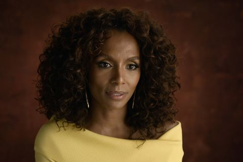 Janet Mock. Black woman with brown shoulder-length curly hair wearing a yellow top.