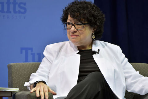 Justice Sonia Sotomayor. A Latinx woman wears a black shirt, black pants and a white blazer as she sits in a gray chair.