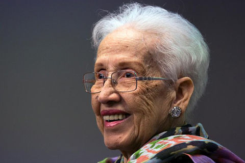 KATHERINE JOHNSON. Elder Black woman with short white hair, wearing glasses and a colorful top.