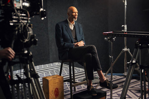 Kareem Abdul Jabbar. Slim older Black man with bald head and gray beard, wearing blue blazer, gray V-neck sweater and pants and a white button down top. He's sitting in chair with legs crossed surrounded by camera equipment.