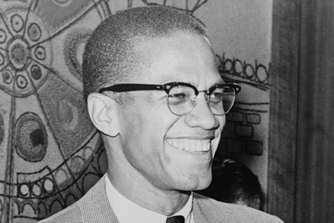 Malcolm X. Black man with short brown hair wearing glasses, white shirt, black tie, tan colored suit jacket, smiling.