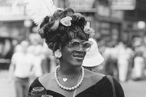 Marsha P. Johnson. Black woman with flowers and feather in hair, wearing glasses, flower earrings, pearl necklace and black sweetheart shaped top.