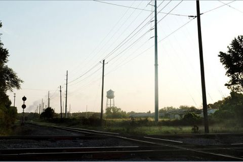Slave auction site. Rural area with train tracks and power lines.