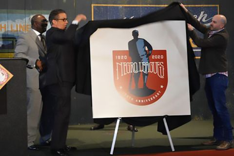Negro League Logo. A white board featuring the logo illustration of a Black baseball player being unveiled by two men.
