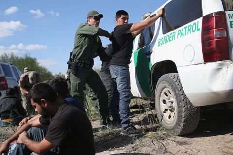 Man stands with his back to border patrol agent as border agent frisks him up against a white border patrol van.