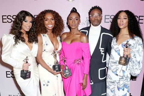 "Cast of ""Pose."" Four Black women wearing gowns and holding trophies and one Black man wearing a black and white suit with a white top and glasses."