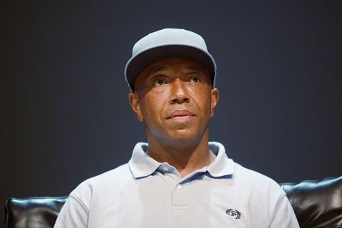 Russell Simmons. Black man wearing light gray baseball hat and light gray shirt.