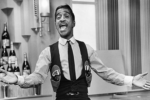 Sammy Davis Jr. Black man with short dark hair singing in a gun-slinger's outfit seated on a bar with his arms extended.