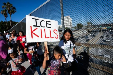 "A young boy stands at a protest and holds a sign that reads ""ICE KILLS"""