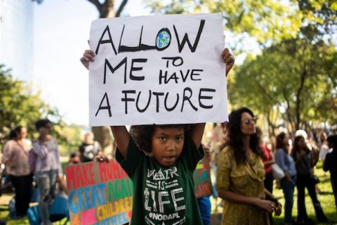 "Black child in black shirt at protest holds white sign that reads, ""Allow me to have a future."""