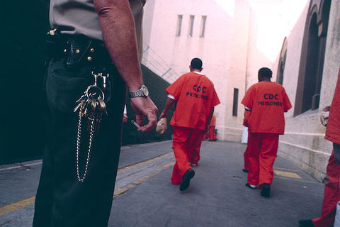 a group of men wearing orange jumpsuits walk away from the camera as a security officer can be seen in the foreground.