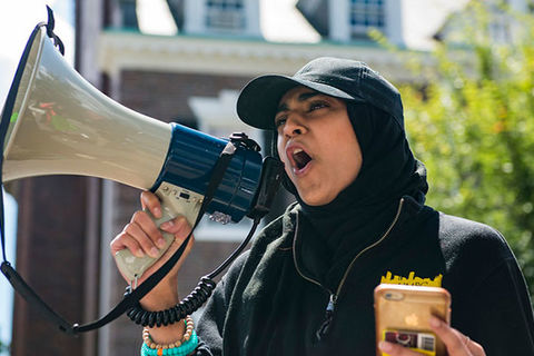 Anti-Hate Report. Muslim woman wearing a black cap over a black headscarf and black top holding a bullhorn.