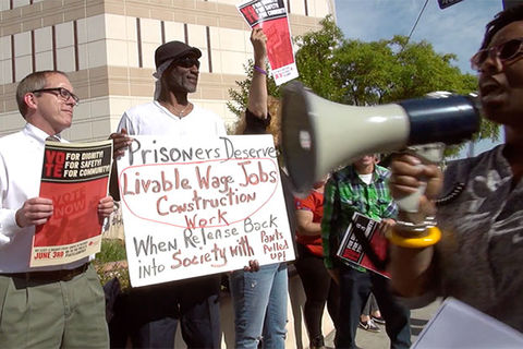 Scene from the documentary 'Bedlam' :  Protest scene where two men, one White, one Black, hold up signs and Black woman walks by speaking on a microphone.