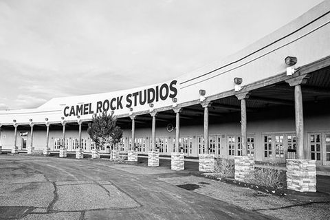 "Camel Rock Studios. Black and white image of an open arena with columns and a sign reading ""Camel Rock Studios."""