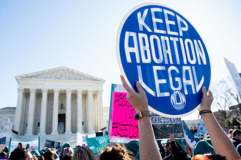 "Protestor in front of the U.S. Supreme Court holds a sign that reads, ""keep abortion legal"""