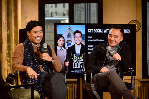 "Randall Park and Melvin Mar. Two Asian American men seated side-by-side holding microphones in front of a TV screen that says ""Fresh Off the Boat."""