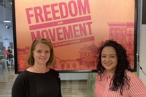 "Two women stand in front of an orange sign that reads ""Freedom of Movement"""