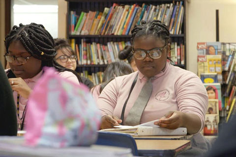 PUSHOUT. Two teenage Black girls in a classroom with book shelves behind them as they sit at a desk wearing pink button up shirts, gray ties, long braids and glasses.
