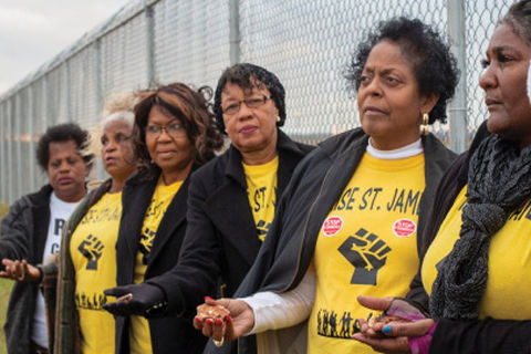 RISE activists. Six older Black women standing side-by-side against a fence holding a hand out, all wearing yellow t-shirts and black jackets.