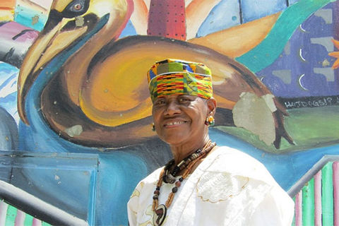Sadie Roberts Joseph. Older Black woman wearing colorful hat with white top and brown beaded necklace, standing in front of colorful wall mural.