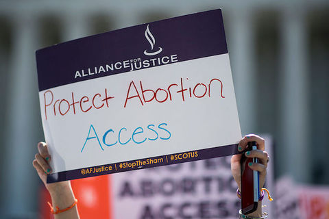 "A person holds a protest sign that reads, ""Protect Abortion Access"""