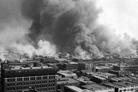 Tulsa Massacre. Black and white photo showing aerial view of buildings on fire and smoke billowing.