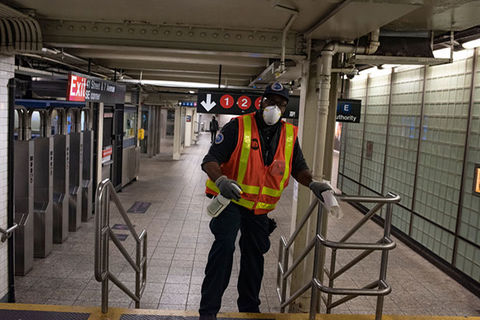 MTA Worker. Man in NYC subway station wearing MTA construction vest, face mask and gloves.