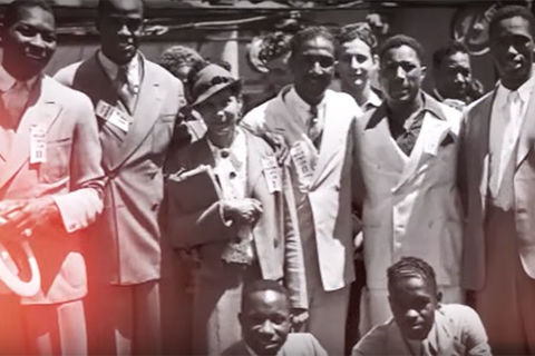 1936 Olympics. Archival image of about nine Black men and women huddled together for a photo with everyone wearing a suit.