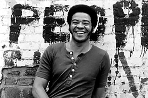 "Bill Withers. Black and white photo with Black man in a short Afro and dark short sleeve t-shirt standing in front of brick wall with ""People"" spray painted on it."