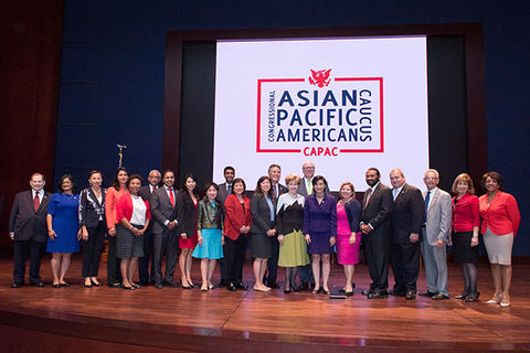 Congressional Asian Pacific American Caucus. Group of congressional employees standing on a stage in front of a blue curtain and sign reading  Congressional Asian Pacific American Caucus.