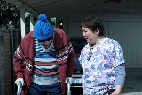 """COVER/AGE"". Older Asian American woman in floral print scrubs assisting an elderly person using a walker."