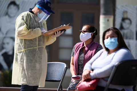 Testing for Coronavirus. A healthcare worker in protective gear, stands and holds a clipboard as two Latinx women sit with masks on