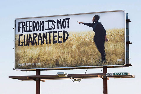 "Billboard. Photo of a young Black man standing in a field of tall grass pointing to words in big black letters that read: ""Freedom Is Not Guaranteed."""