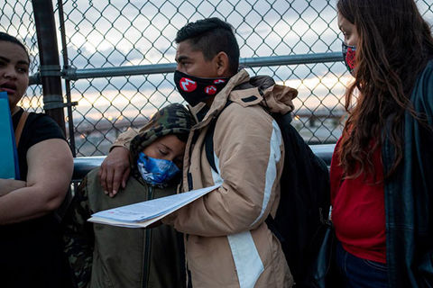 Immigration. Latinix father wearing tan coat and black face mask stands in front of gate with young boy leaning on him, also wearing a mask, and Latinx woman wearing red shirt and black jacket, with a face mask.