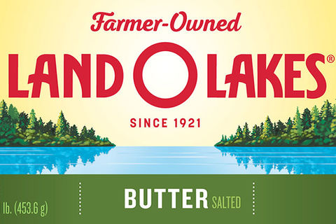 Land-O-Lakes. Packaging for butter that has yellow background with green trees alongside a blue lake.