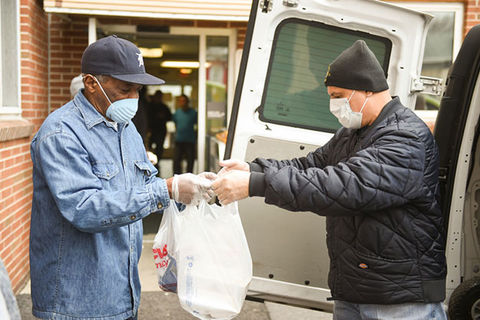 Latinx Community. Elderly man wearing blue shirt and baseball cap accepts food from the back of a white truck, where a man in black stands handing out food.