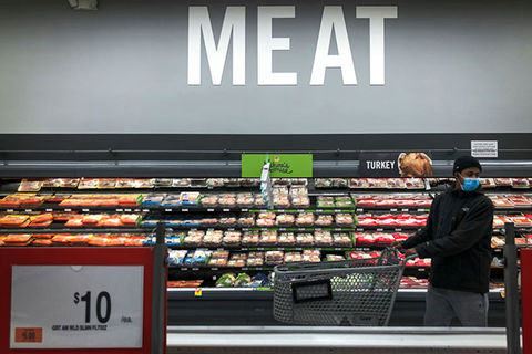 "Meat. Black man wearing blue face mask, dark jacket and blue jeans, in a supermarket in front a sign that reads, ""Meat."""