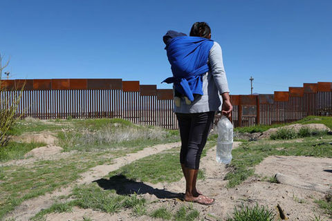 Migrant. Rear view of woman with dark hair wearing gray top, dark leggings and carrying a child in a blue blanket and a large bottle of water, facing the U.S./Mexico border wall.