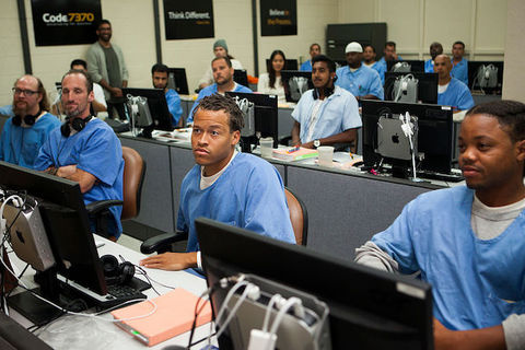 A group of Black men wearing blue prison uniforms sit in front of computers in a classroom setting.