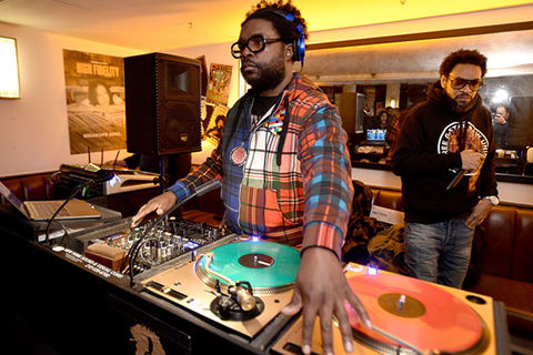 Questlove. Black man with short dark hair DJ'ing, wearing headphones, an orange and blue plaid shirt and dark framed glasses.