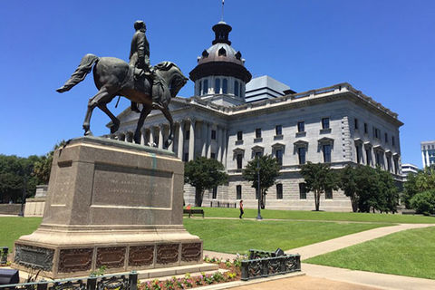 South Carolina. Foreground image of a statue showing man on horse with district court building in the background.