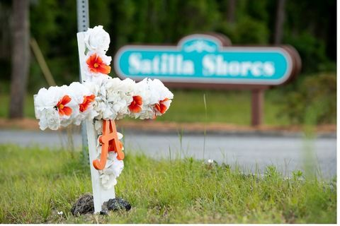 "Ahmaud Arbery. A white-and-red-flowered cross and the letter ""A"" sits in the ground at the entrance to the Satilla Shores neighborhood where Ahmaud Arbery was shot and killed"