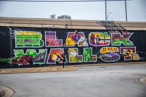 "Black Wall on side of highway with the words ""Black Wall St."" in thick block graffiti color letters against a black wall"
